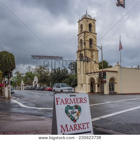 Downtown Ojai Tower Closest To Winter Rain Clouds As Sign Points Way To Local Farmers Market.  Shot