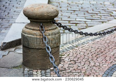 fencing of sidewalk in form of posts with iron chains
