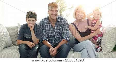 Young couple with their cute kids having rest at home
