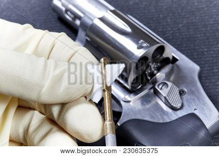 Hand Inserting A Cotton Patch Into A Gun Cleaning Rod