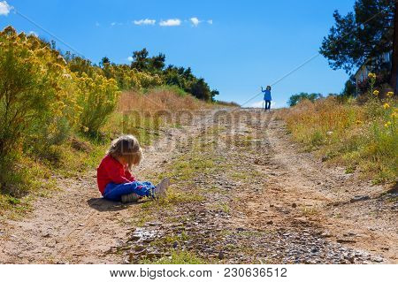 A Very Young Girl Sits In The Rut Of A Path In The Middle Of A Hill With Her Head Down, Pouting Beca