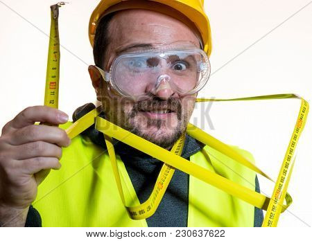 juggling a man who wants to do a work without knowledge, work without experience. Do it yourself, man dressed in yellow builder helmet with protective glasses ready to start the construction work