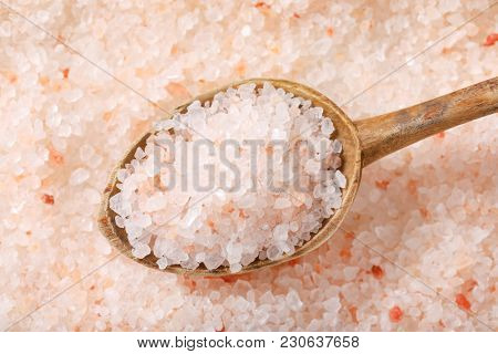 spoon of coarse grained salt on coarse grained salt background