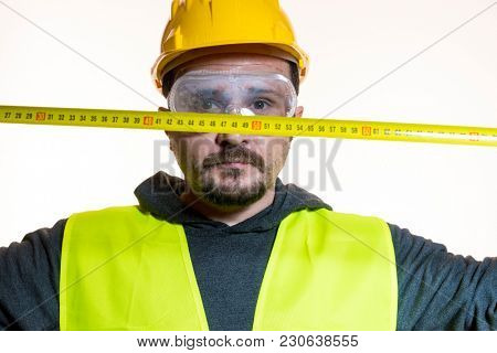 taking measurements with a meter, a man who wants to do a work without knowledge, work without experience. Do it yourself, man dressed in yellow builder helmet with protective glasses