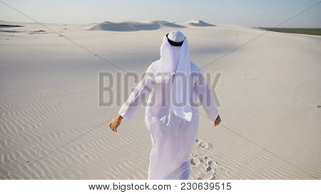Confident Muslim Guy Arabian Uae Sheikh Stands Full-length In Middle Of Bottomless Desert With White