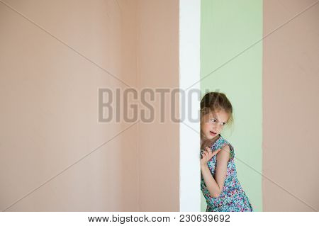 Beautiful Small Girl Hid Behind The Corner In New Room
