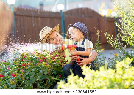 Pretty Woman And Her Child Son Watering Flowers With Water Hose In The Yard