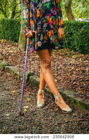 Young Woman Stands With Walking Stick In Floral Dress