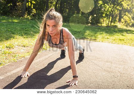 Fit Woman Doing Push-ups At The Park