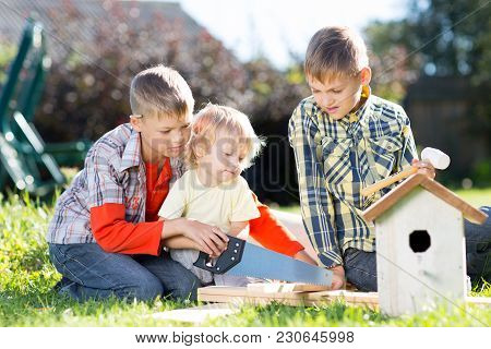 Kids Brothers Making Wooden Birdhouse By Hands. Older Child Teaches His Younger Brother.