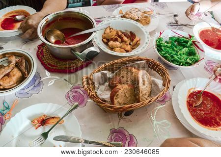 Top View Of Family Gathering Together At Home For Eating Dinner.
