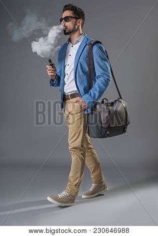 Full Length Of Attractive Businessman With Brief-bag And Smoking Electronic Cigarette On Move