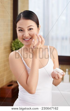Cheerful Young Asian Woman Applying Hydration Lotion On Her Face
