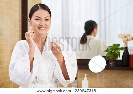Smiling Beautiful Woman Applying Enriched Face Cream