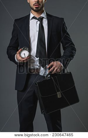 Shocked Young Bearded Man In Business Suit Holding In Hands Snooze And Brief-bag. Isolated On Gray B