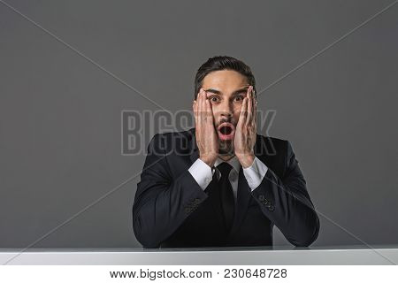 Wow. Waist Up Portrait Of Surprised Discouraged Businessman Sitting At The Desk. Copy Space In Left