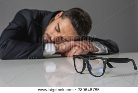 Focus On Glasses. Sleeping Overworked Businessman In Suit Lying On White Table And Sleeping