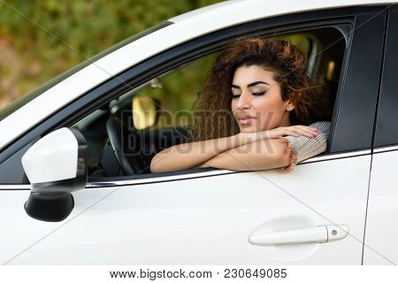 Young Arabic Woman Inside A White Car With Eyes Closed