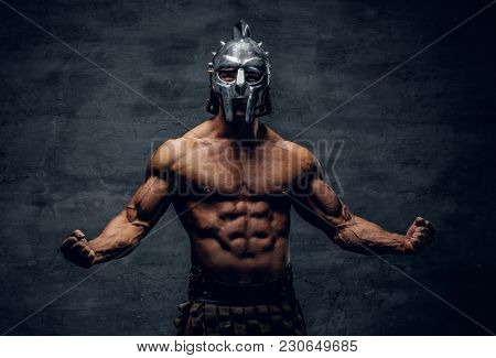 Brutal Shirtless Muscular Male In A Gladiator Silver Helmet On Grey Background.