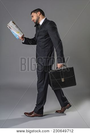 Occupied Stylish Man. Full Length Of Overworked Businessman Going And Holding Cellphone With Shoulde