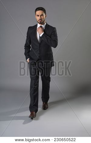 Full Length Portrait Of Concentrated Bearded Man In Business Suit Touching Up Tie. He Looking At Cam