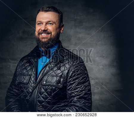 Studio Portrait Of Bearded Male Dressed In A Blue Shirt, Black Jacket And A Bow Tie Over Grey Backgr