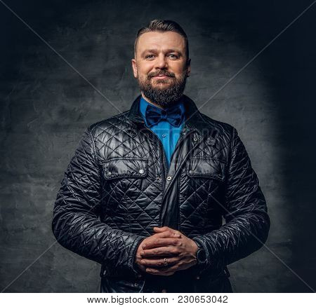 Portrait Of Smiling Bearded Male Dressed In A Leather Jacket And Bow Tie.