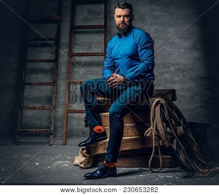 Full Body Studio Portrait Of Stylish Bearded Male Dressed In A Jeans, Blue Shirt And Bow Tie Sits On