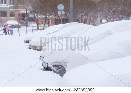 Cars Completely Covered With Snow On Parking In The City Yard During Snowfall.