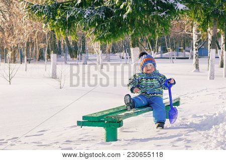 Little Baby With A Shovel Walking Alone In The Park. Winter Season.