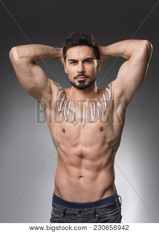 Waist Up Portrait Of Serious Muscular Man With Naked Upper Body Holding Hands On Back Of His Hand. I