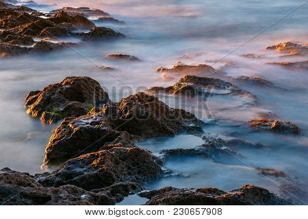 Long Exposure Of Sea And Rocks At Sunset