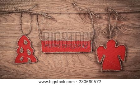 Christmas Greetings Attached To A Rope On A Wooden Background. Place For Text