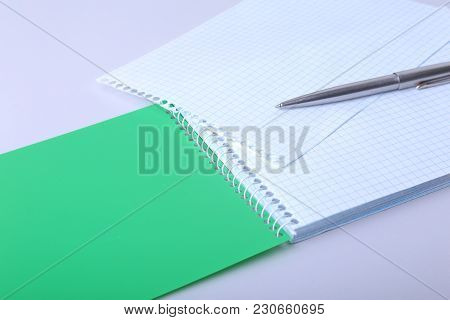 Hands Wresting The Sheet Of Paper Out Of A Spiral Notebook