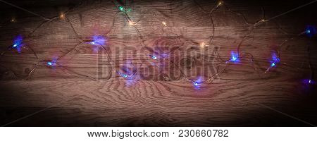 Christmas Tree Garland Laid Out On A Wooden Table .festive Background
