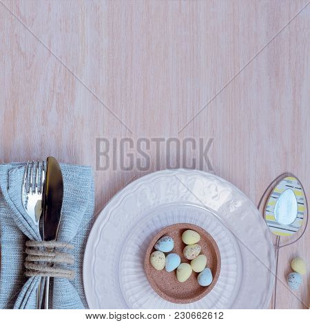 Happy Easter concept. Top view of beautiful spring table settings in pastel tone, blue linen napkin