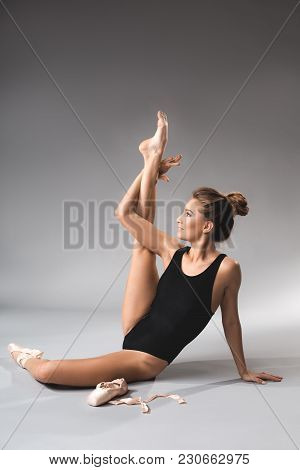 Ballerina In Leotard Sitting On The Floor And Demonstrating Stretching Of Legs With Smiling Face