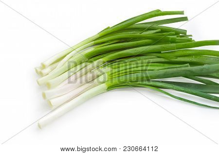 Bunch Of The Several Washed And Peeled Stalks Of The Green Onion With Drops Of Water On A White Back