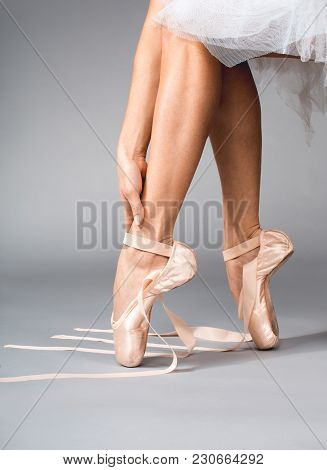 Close Up Of Female Hand Running Her Slim Legs Shod In Ballet Shoes