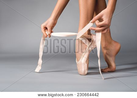 Close Up Of Ballerina Feet Standing On Tiptoe And Tying Satin Strips On Pointe