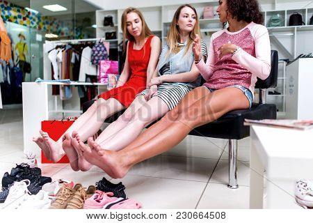 Young Smiling Girlfriends Sitting In A Clothing Store Looking At Their Bare Feet And Pile Of New Sho