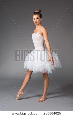 Full Length Portrait Of Female Dancer Standing In Ballet Skirt And Straightening One Foot