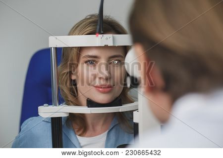 Portrait Of Smiling Female Client Checking Eyesight With Equipment Opposite Doctor. Ophthalmology Co