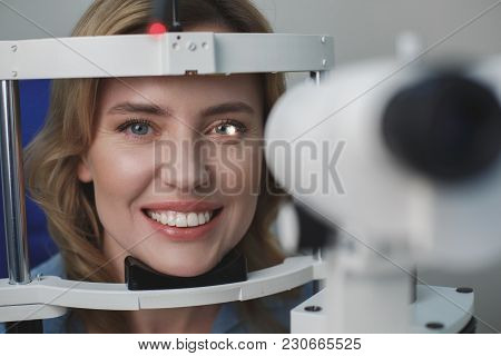 Portrait Of Close Up Cheerful Female Face Examining Eyesight With Equipment. She Looking At Camera.