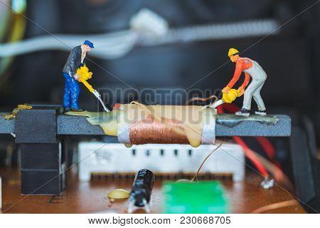 Miniature People : Worker Team Repairing Electronic Circuits.