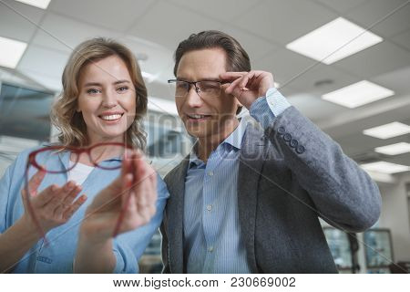 Low Angle Portrait Of Beaming Husband And Wife Watching At Spectacles While Standing In Optician Sho