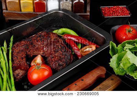 fresh glazed baked big beef meat rib chunk under sweet sauce with lettuce broccoli tomatoes hot chili pepper pink peppercorn different spices on black wooden table