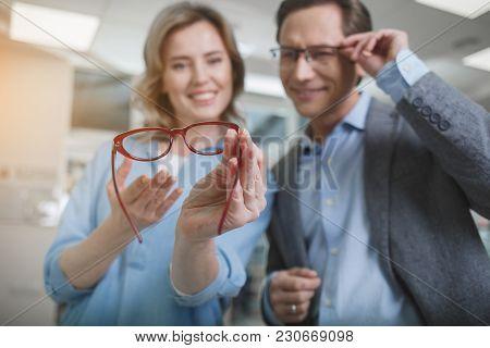 Portrait Of Cheerful Woman And Male Choosing Eyeglasses In Shop. She Keeping It In Hands. Eyesight C