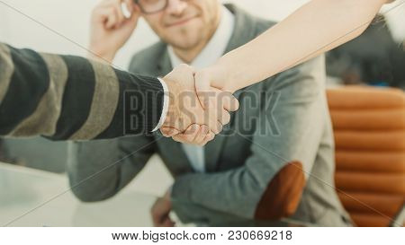 Handshake Of Business Partners On The Background Of The Professional Employee.the Photo Has A Empty