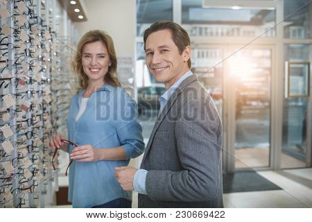 Portrait Of Beaming Wife And Husband Choosing Glasses While Standing In Shop. Eyesight Concept